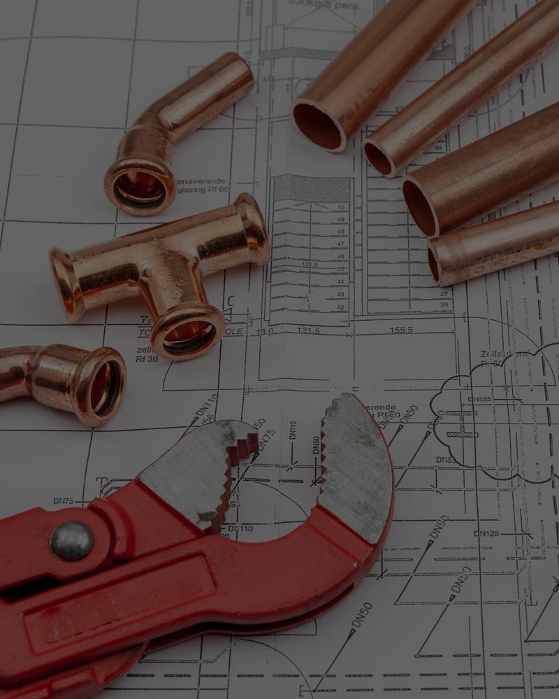 Fotografía en primer plano de herramienta y tuberías de cobre sobre un plano