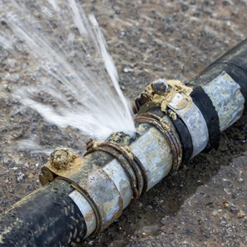 Fotografía en primer plano de una tubería que tiene una enorme fuga de agua